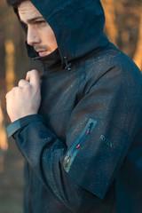 Man in waterproof jacket walking in woodland on an evening