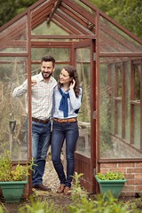 Couple in greenhouse allotment wearing country shirts