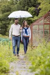 Couple in allotment walking under umbrella