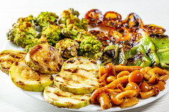 Fresh grilled vegetables and pickled mushrooms on a white plate