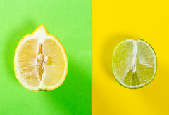 Half a lemon on a green background and half a lime on a yellow won