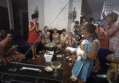 40.  In Texas, Pat Collins (in red), the wife of the Apollo 11 astronaut Mike Collins, celebrates while watching the splashdown and the successful end of the mission with a houseful of friends.