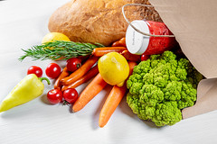 Brown paper shopping bag filled with fresh products and vegetables
