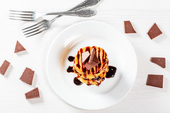 Fried pancakes with chocolate topping and pieces of chocolate on the table with forks