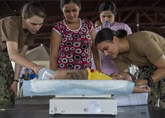 Sailors weigh a patient at a temporary medical treatment site.