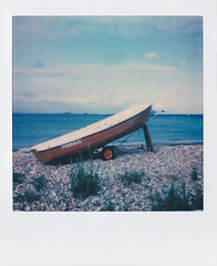 Polaroid of a Small Boat on a Pebble Beach