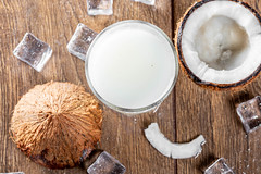 Glass of coconut milk with fresh coconut and ice on a brown wooden background