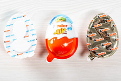 Child kinder joy whole and two halves in packages on the table