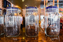Close up of various coffee beans in sealed jars