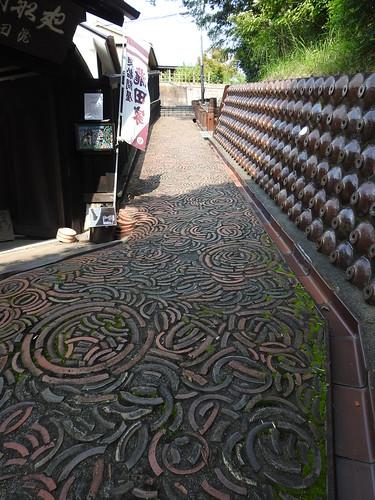Takita family ceramic shards walkway and jug walls