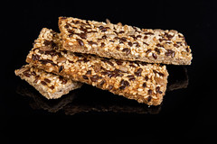 Healthy Bars with Sesame Sunflowers Seed and other cereals above black background