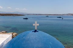 View over the blue dome with white cross of St. John's of Deti Church, to motorboats in the Mediterranean Sea at Paros, Greece
