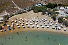 Luftbild vom Monastiri Sandtrand, mit Sonnenliegen und Sonnenschirmen an der Küste von Paros