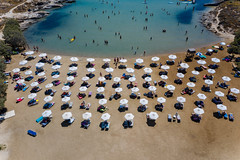 People swimming in the Mediterranean Sea and laying on beach chairs, under white parasols, at the white sandy Monastiri Beach on Paros