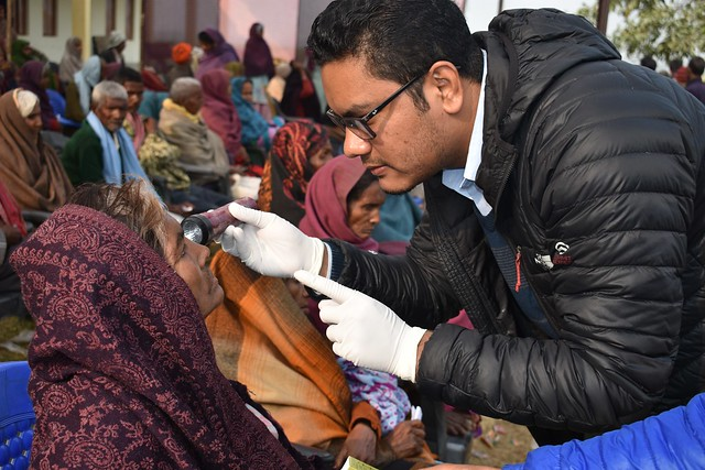 Ophthalmologist Examining eyes of Post Cataract Surgery patients from free surgical camp happened a day before.