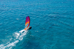 Aerial view shows a water sportsman windsurfing in the blue Mediterranean Sea, in front of Santa Maria Beach on Paros, Greece
