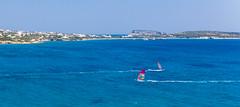Zwei Windsurfer surfen in entgegengesetzte Richtungen, vor der Santa Maria Strandküste von Paros, Griechenland