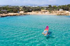 Luftbild zeigt einen Wassersportler beim Windsurfen im türkisfarbenen Mittelmeer, vor dem Santa Maria Strand auf Paros, Griechenland