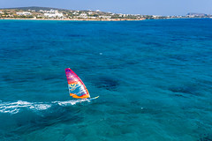 Windsurfer auf einem Surfbrett mit buntem Segel auf dem klaren Meer vor Paros, Griechenland