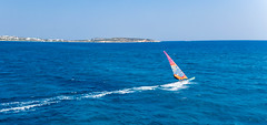 Water sports enthusiast windsurfing over the waves of the blue Mediterranean Sea in front of the Greek island of Paros