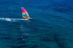 Single windsurfer doing watersports in the deep blue Aegean Sea
