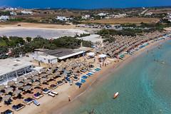 Luftbild zeigt Santa Maria Strand voller Touristen im Sommerurlaub, unter Sonnenschirmen aus Bast