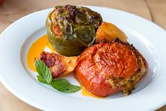 Nahaufnahme von schrumpeligen gefüllte Tomate, mit Paprika, mit mediterraner Reisfüllung, Pinienkerne, Rosinen und Minze, auf einem weißen Teller