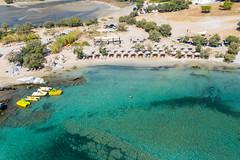 Luftbild der grünen Mittelmeers, bunte Tretboote mit Rutsche und der weiße Strand von Kolimbithres auf der griechischen Insel Paros