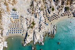 Luftaufnahme zeigt den Felsenstrand Kolimbithres auf Paros, mit Sonnenschirmen am weißen Sandstrand am grünen Mittelmeer