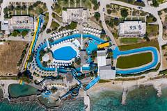 Luftbild des Aqua Paros Wasserparks auf einer griechischen Insel, mit Pool und Wasserrutschen, direkt am Mittelmeer