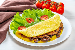 The concept of Breakfast. Egg omelet with mushrooms and vegetables