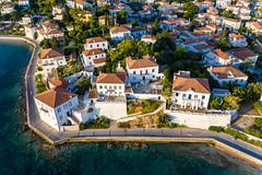 Luftbild der Küstenstraße auf der malerischen Insel Spetses, vor aristokratischen, neoklassizistische Wohnhäusern, im Argolischen Golf
