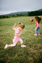 Children playing with a ball and running on a big field