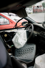 A damaged car with a deployed airbag