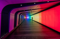 Image by NoVice87 (92110231@N03) and image name Kings Cross Colour photo  about The foot tunnel from St pancras Square into Kings Cross Underground Station illuminated in 'Pride' colours.  So much fun with a camera but it did take quite a while for the right person to come along without there being hordes of selfie-takers in the way!