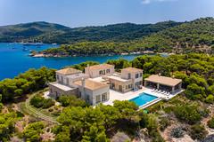 Luftbild einer mehrstöckigen Villa mit privatem Pool und Gartenanlage, umgeben von wilder Natur, auf der griechischen Urlaubsinsel Spetses