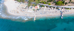 Aerial picture of empty sun chairs at Kaiki Beach, Spetses, with small waves at the island shore