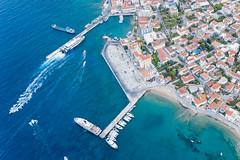 Drohnenbild von Schiffen und Booten an Landungsstegen und einem Wassertaxistand in einer Bucht im blauen Meer