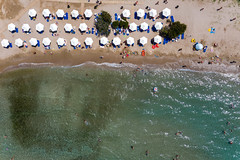 Aerial view of tourists and families on vacation at a public beach, with colorful dinghy, inflatable air mattresses and water toys