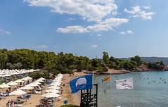 Urlauber am Strand des Aks Hinitsa Bay Hotels in Chinitsa, mit Strandliegen und weißen Sonnenschirmen