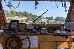 Decorated steering room with wooden steering wheel, of a ship on Greek waters with view of a rocky coast