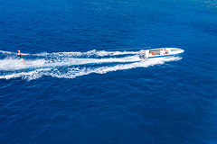 Drone picture of a water sports enthusiast on water skis, pulled by a motor sport boat across the blue sea and breaking white waves