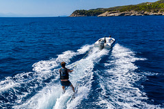 Drone picture of a water skiing at the rocky bay near Agii Anargir of the Greek holiday island Spetses