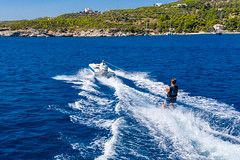 Blue-white water ski boat pulling a water sports man across the deep blue sea, in front of the rocky beach of Spetses, Greece