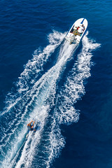Top view of man on waterskis during vacation, motor sports boat and breaking waves on the blue sea of Argolic Gulf