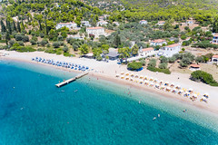 Aerial picture of Parasols and sun chairs separated by color, at Paralia Agii Anargiri Beach on Spetses, Greece