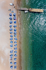 Aerial view shows neatly placed parasols in blue and white, in two rows, at the sandy beach of Agii Anargiri & green sea