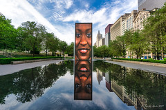 Image by NettyA (7272097@N08) and image name Crown Fountain photo  about Early morning (about 8am when it first starts up) at Crown Fountain in Millennium Park, Chicago. The fountain shows a continuing array of local people's faces. After a few minutes of each face, water comes out of their mouth. My favourite for her beautiful smile.   Explore # 19