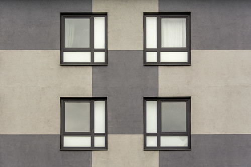 Four windows in a grey and beige facade