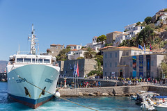 Tourists disembark from Comos passenger ship and walk over a rocky pier Limani Ydras, to the Historical Archive Museum of Hydra, Greece